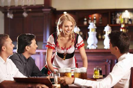 brings: La cameriera porta la birra a giovani uomini