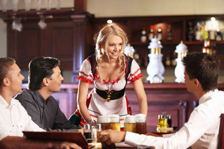 The waitress brings the beer to young men Stock Photo - 8096781
