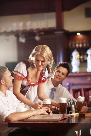 beer bar: Young waitress brings the beer bar visitors