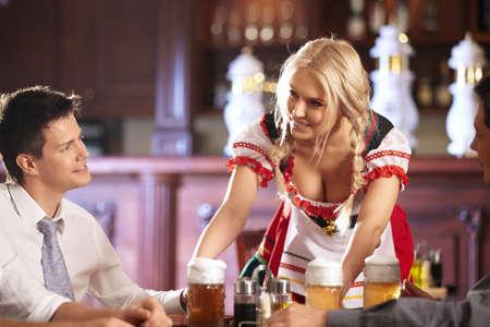Young waitress brings beer to visitors photo