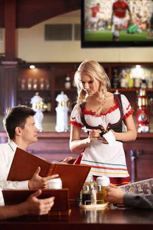 hombre tomando cerveza: Joven camarera escribe una orden en un restaurante
