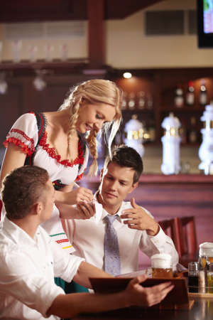 A young attractive waitress takes an order at a restaurant photo
