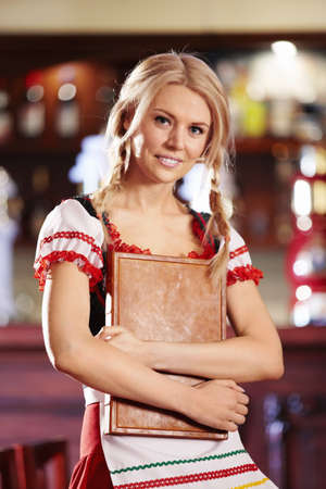 A pretty young waitress holding menu in his hand photo