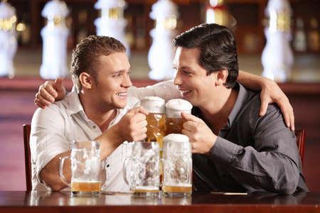 hombres gays: Dos hombres gays borrachos con una cerveza en un pub