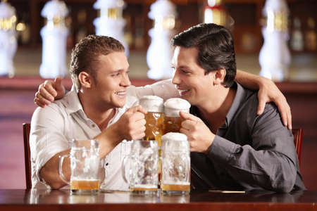 Two drunken gay men with a beer in a pub photo