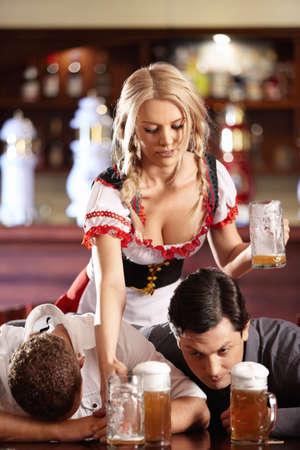 borracha: Joven camarera borra la vajilla sucia, hombres borrachos en un pub