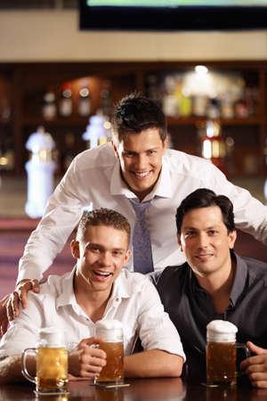hombre tomando cerveza: Tres hombres j�venes felices en la barra de