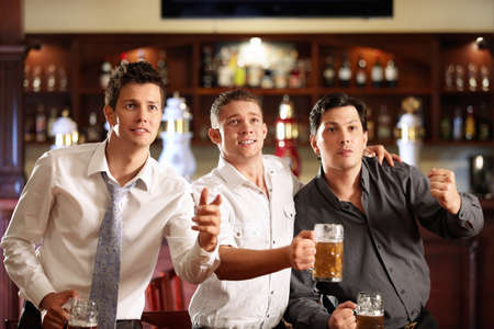 horizontal bar: Young men with a beer watching the match in the bar