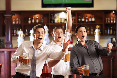Young people with beer watching football in a bar photo