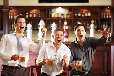 horizontal bar: Young men rejoice the victory of his team in a bar