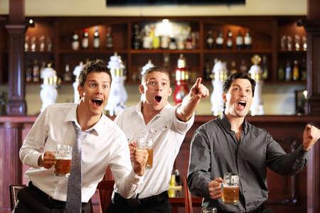 vasos de cerveza: Tres hombres con cerveza alegrarse de la victoria de su equipo favorito en el pub
