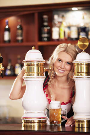 Young attractive girl pours a beer at the bar photo