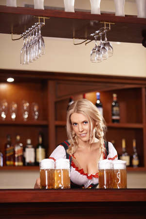 The nice girl behind the bar with beer photo