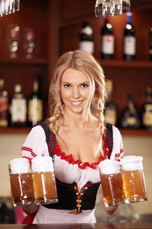octoberfest: Una camarera bonita con cervezas en el bar  Foto de archivo