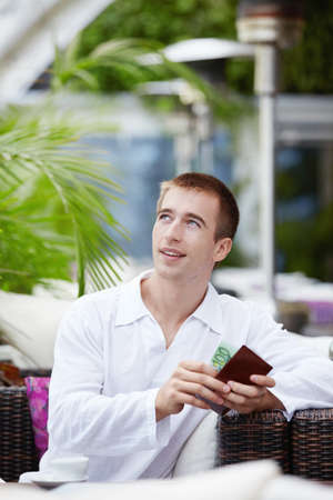 gets: Man gets money from her purse at a restaurant Stock Photo
