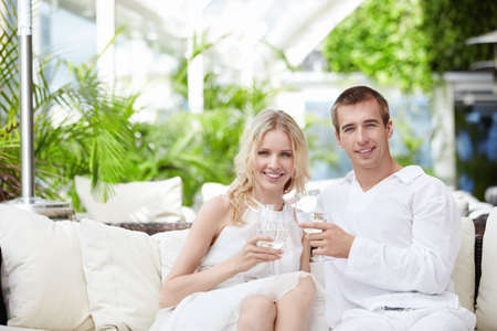 Young attractive couple drinking water in a restaurant Stock Photo - 8096704