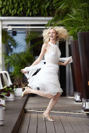 A beautiful young girl jumping in a restaurant photo
