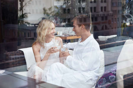 Enamoured young couple at restaurant through glass photo