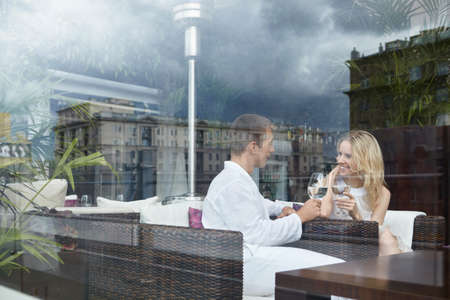 Young attractive couple behind glass in a restaurant Stock Photo - 8096777