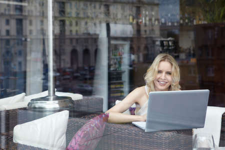 Happy young girl with laptop in restaurant photo