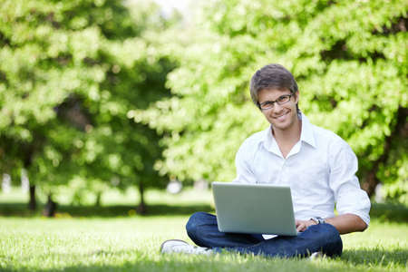 field glass: A young man with laptop outdoor