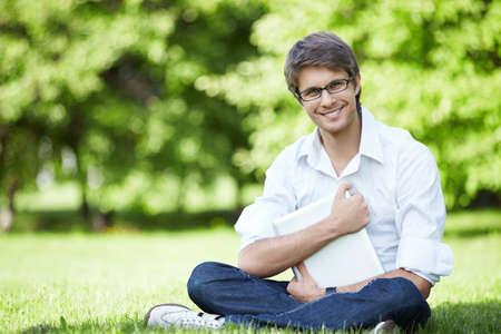 Un joven empresario con un ordenador portátil en la hierba  Foto de archivo