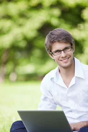 field glass: A smiling young man with laptop outdoor