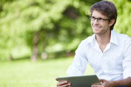 gente sentada: Un hombre sonriente con port�til al aire libre