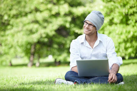 Attractive young man in a hat with a laptop outdoors photo