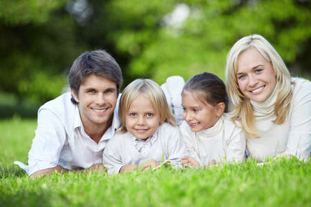 Young families with children lying on the grass in the park photo