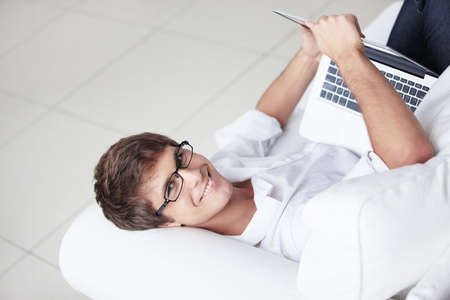 A young man in glasses with a laptop  photo