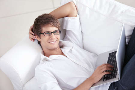 Attractive man with laptop on a couch photo
