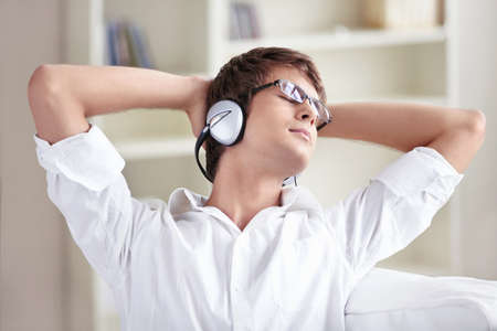 A man listens to music on headphones at home Stock Photo - 8096648