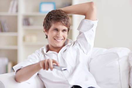 A smiling man changes channels control photo