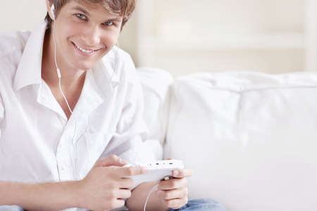 playstation: A man with headphones playing console Stock Photo