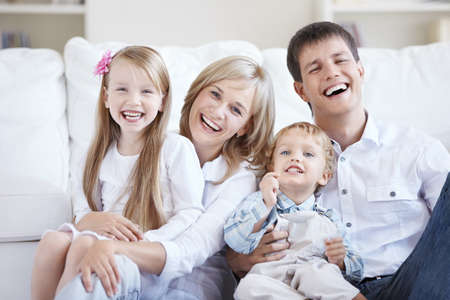 Smiling young parents with two children at home photo