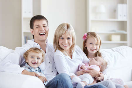 family sofa: A happy family with three children at home