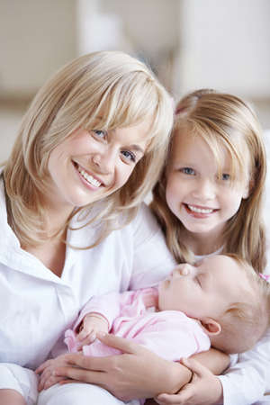 Mom holding the baby in her arms and her daughter photo