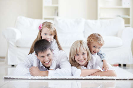 family on couch: Merry parents with children at home