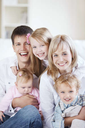 A happy family with kids on the couch at home photo