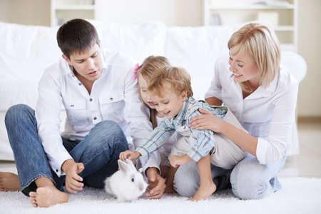 Los niños y padres ven la conejita de casa