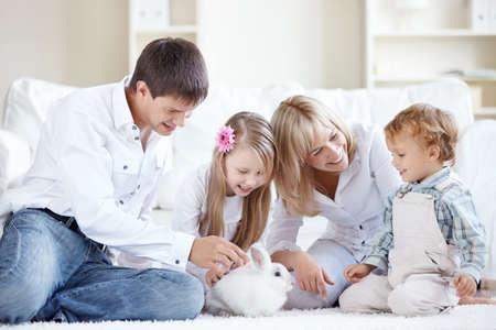 lapin blanc: Regarder la jeune famille � la maison un lapin  Banque d'images