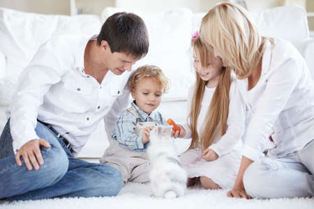 A happy family with children feeding a pet photo