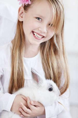 lapin blanc: La petite fille tenant un lapin blanc Banque d'images