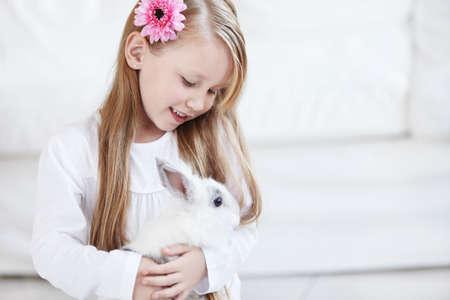 young rabbit: Petite fille tenant un lapin blanc duveteux
