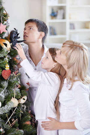 The family dresses up a fur-tree by Christmas photo