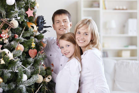 The smiling family of three people close to the spruce photo