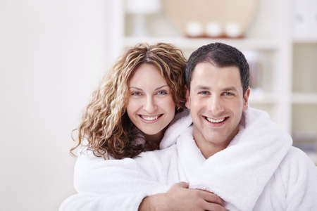 woman bathrobe: Young smiling couple in dressing gowns at home