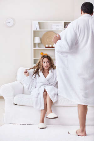 nude girl sitting: Young surprised girl and a man opened its robe Stock Photo
