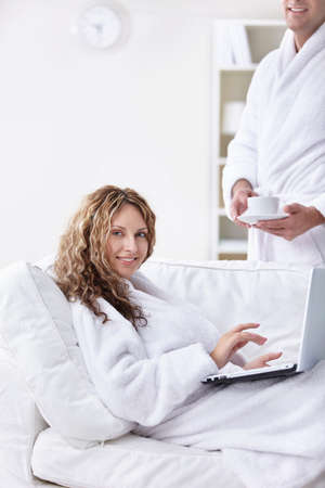 A man in a robe brings coffee girl with laptop photo